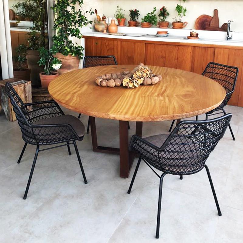 Mesa de jantar redonda em madeira maciça, acompanhada de cadeiras tramadas pretas