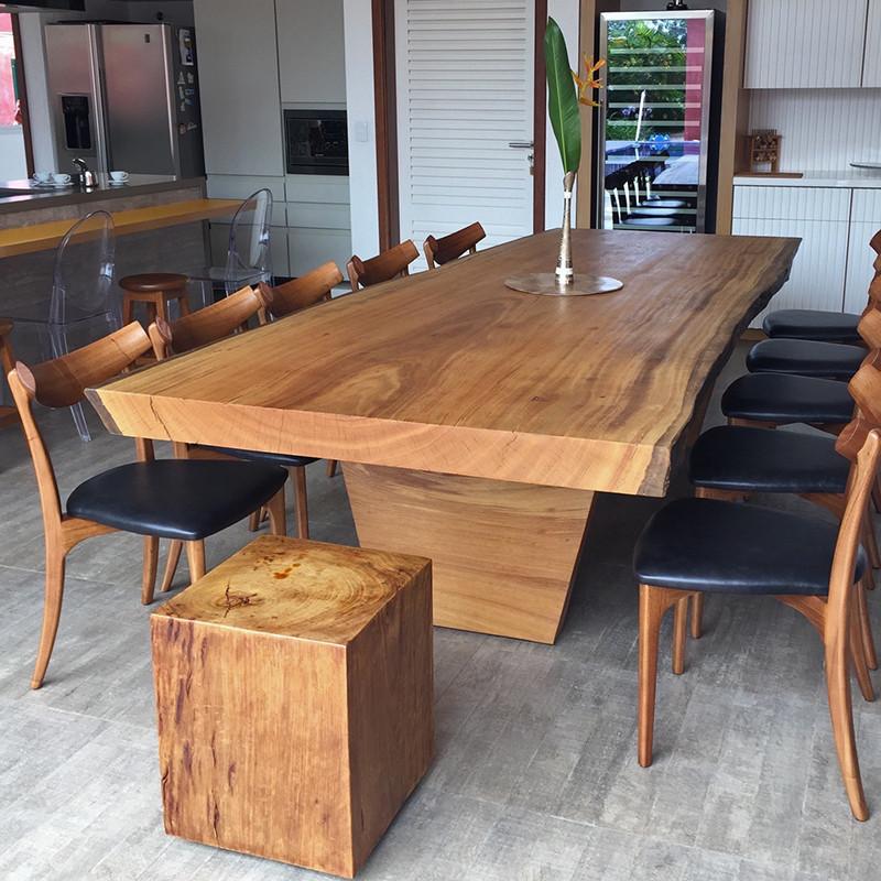 Mesa de jantar em madeira maciça com pés também em madeira, acompanhada de cadeiras de madeira com estofado preto