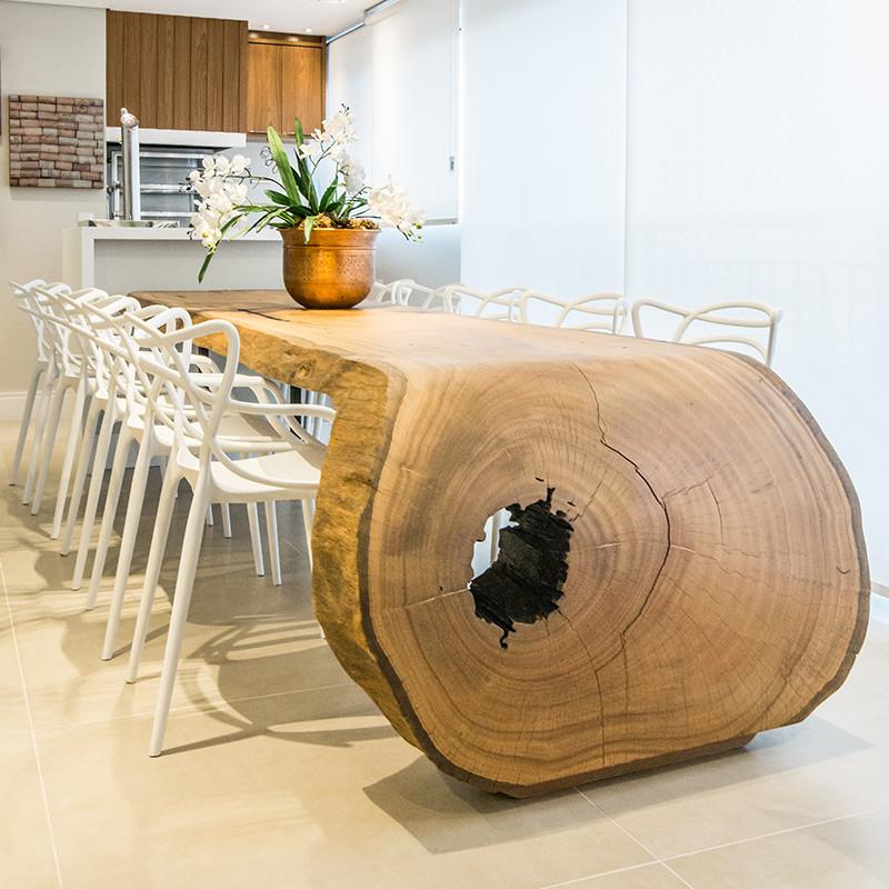 Mesa de jantar em madeira maciça curva, acompanhada de cadeiras de brancas
