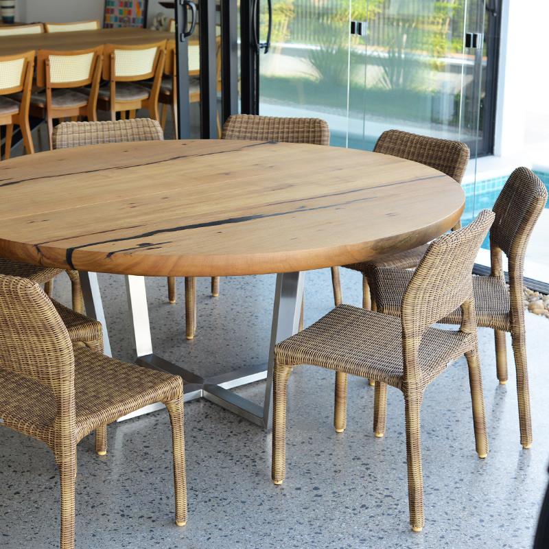 Mesa de jantar redonda em madeira maciça com pé central em inox, acompanhada de cadeiras de fibra trançada