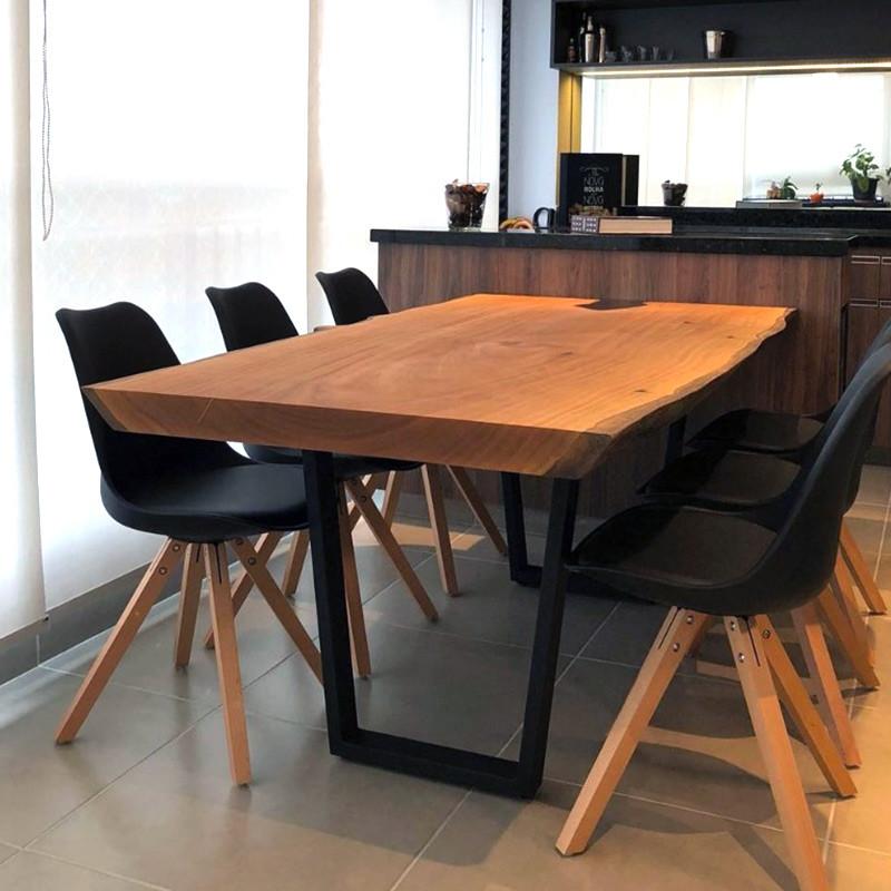 Mesa de jantar em madeira maciça com pés em aço carbono, acompanhada de cadeiras de pretas