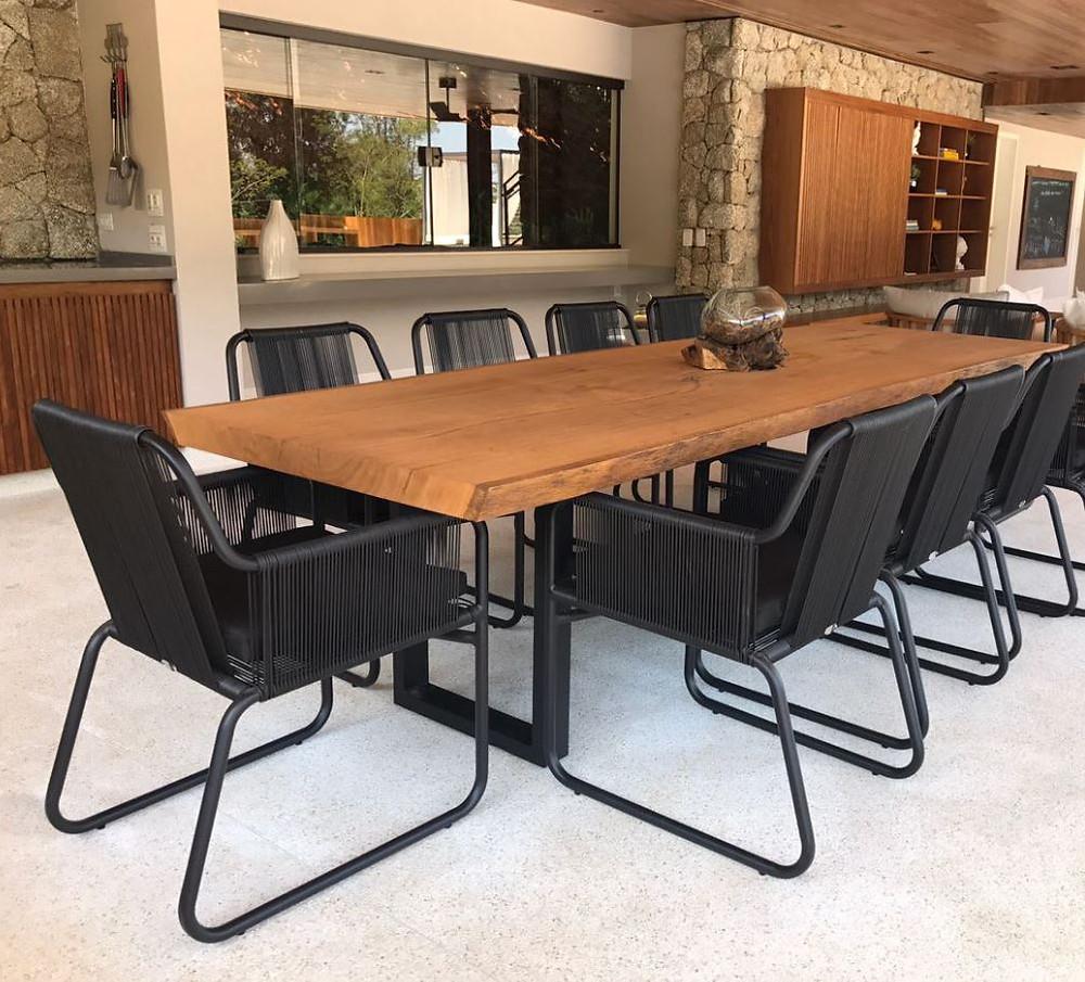 Mesa de jantar em madeira maciça acompanhada de cadeiras pretas