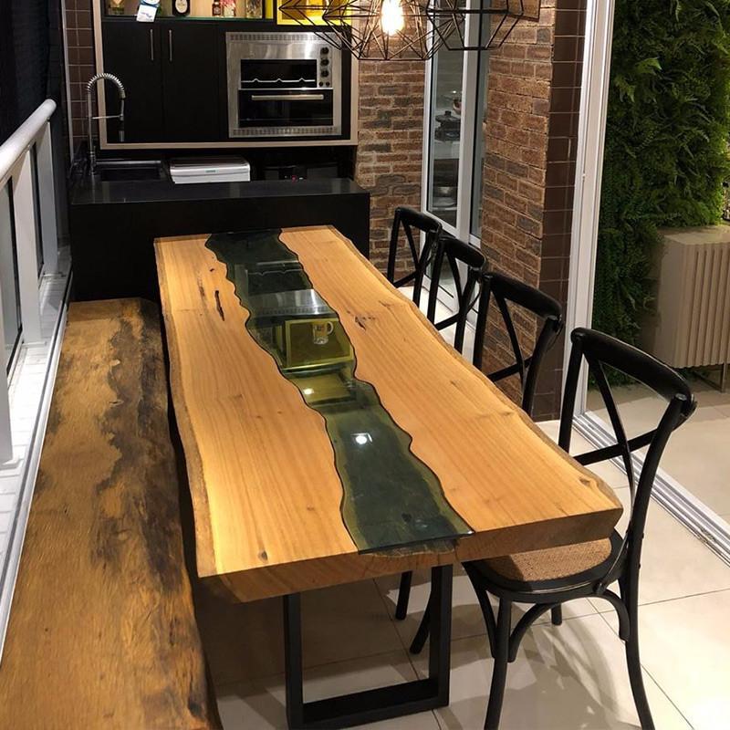 Mesa de jantar em madeira maciça com detalhe em vidro, acompanhada de cadeiras pretas
