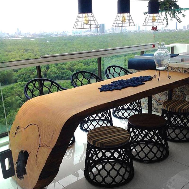 Mesa de jantar em madeira maciça curva, acompanhada de cadeiras e puffs em corda