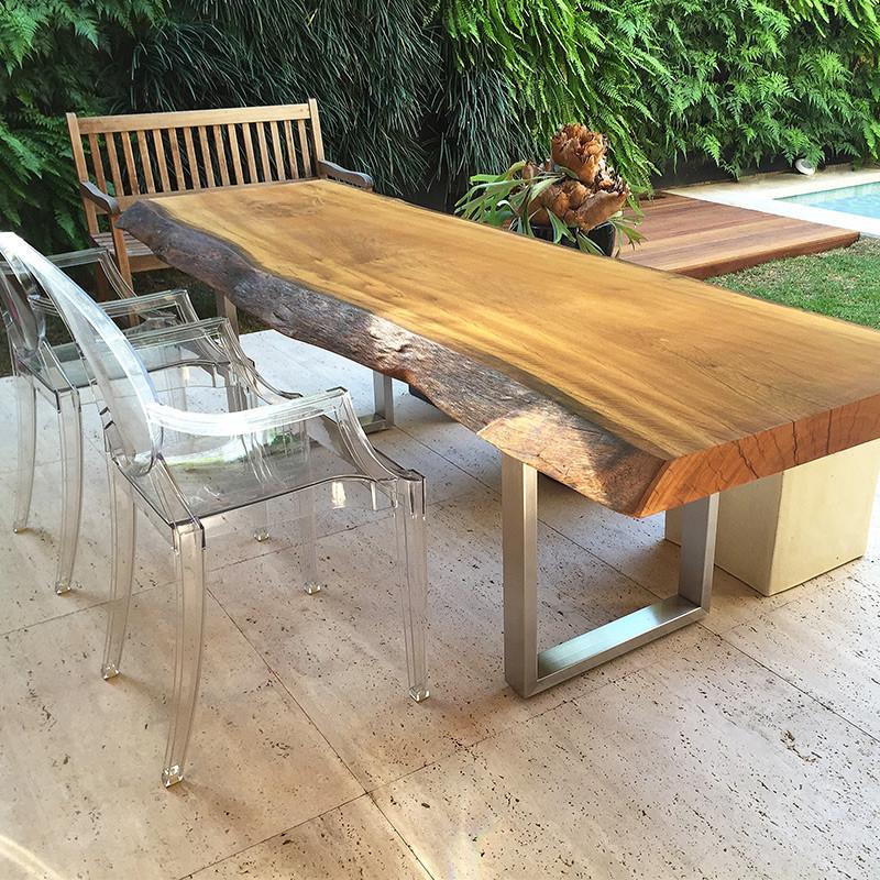 Mesa de jantar em madeira maciça com pés em inox, acompanhada de cadeiras transparentes