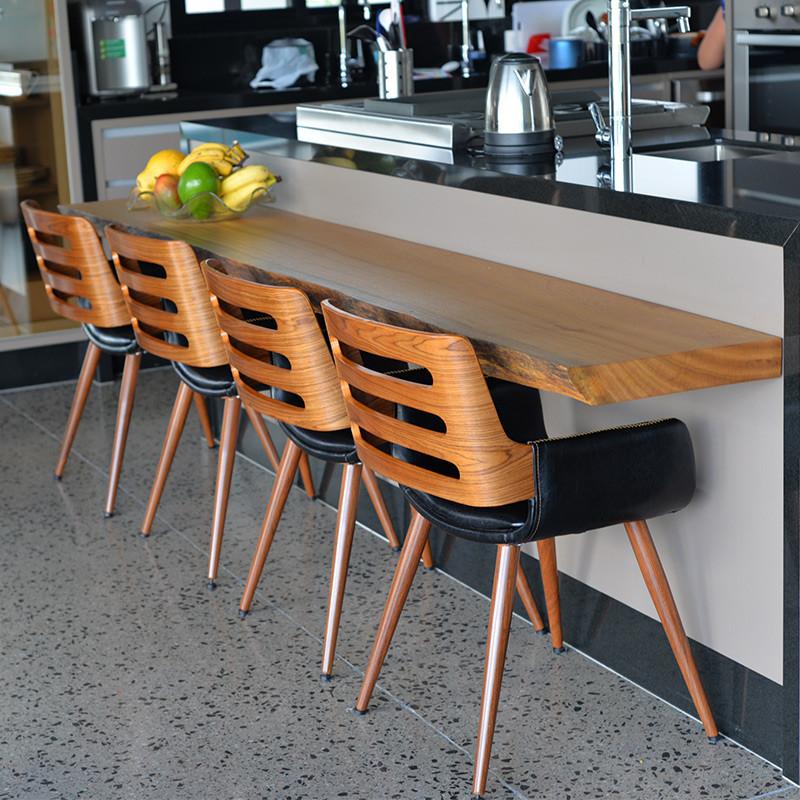 Aparador em madeira maciça, acompanhado de cadeiras que combinam madeira e estofado preto