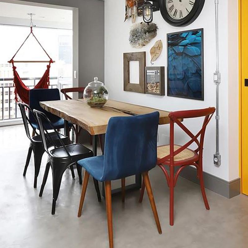 Mesa de jantar de madeira maciça combinada com diferentes tipos e cores de cadeiras.