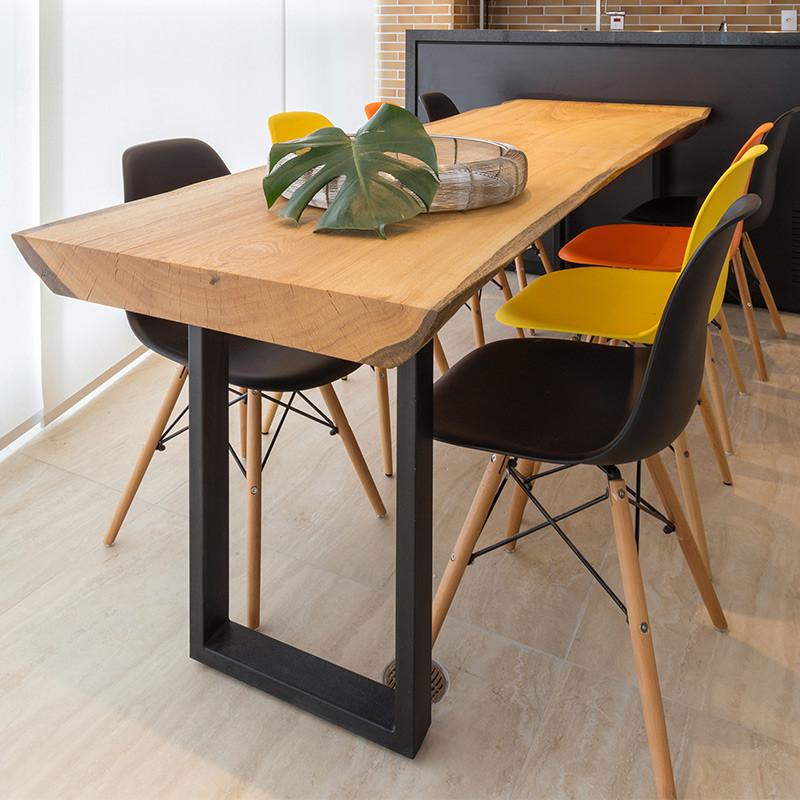 Mesa de jantar em madeira maciça com pés em aço carbono, acompanhada de cadeiras de multi coloridas