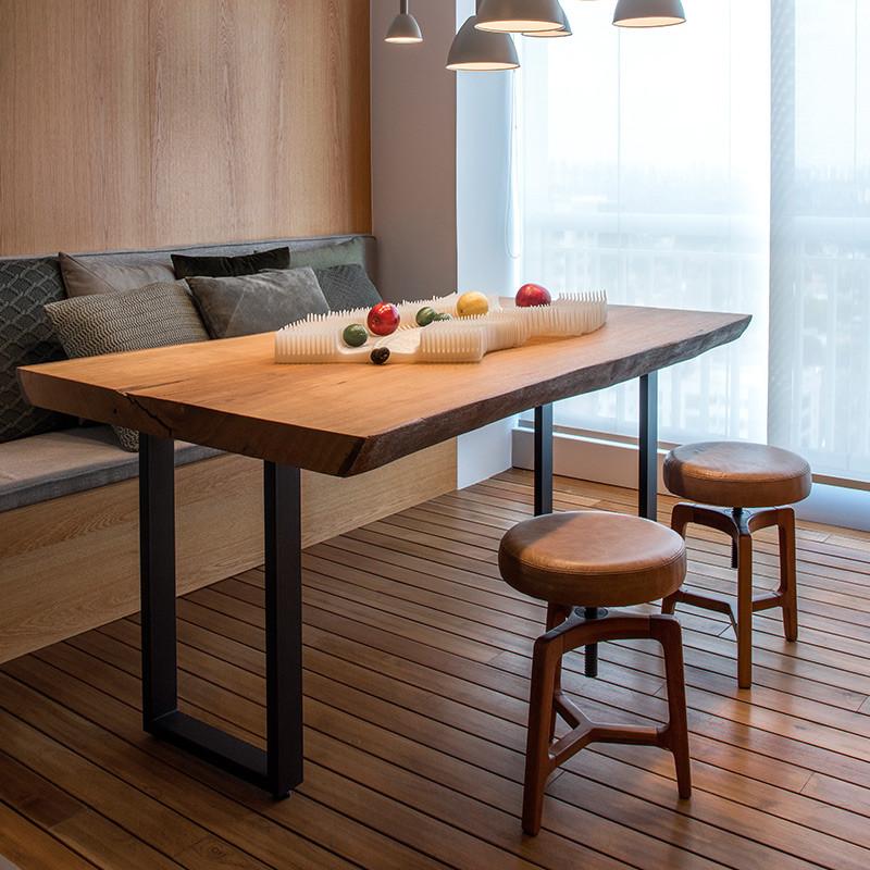Mesa de jantar em madeira maciça com pés em aço carbono, acompanhada de banquetas