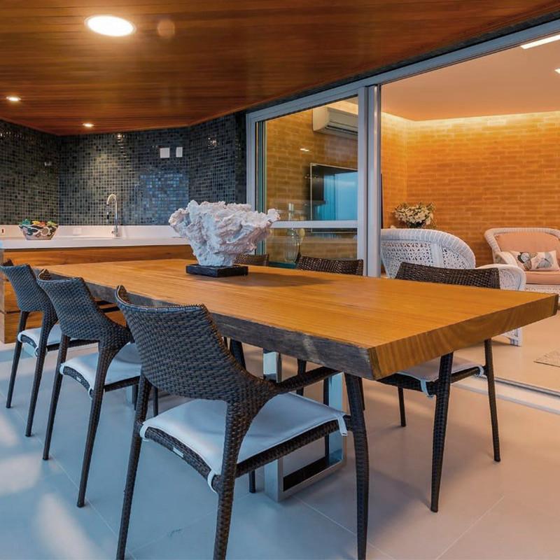 Mesa de jantar em madeira maciça com pés em inox, acompanhada de cadeiras trançadas