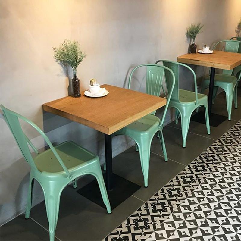 Pequena mesa de jantar em madeira maciça com pé central em aço carbono, acompanhada de cadeiras metálicas verdes