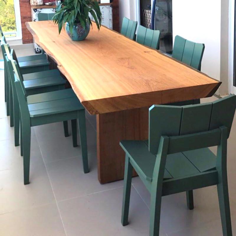 Mesa de jantar em madeira maciça com pés em madeira, acompanhada de cadeiras verdes