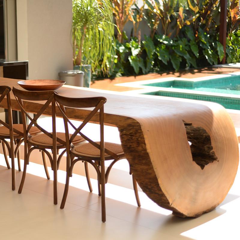 Mesa de jantar em madeira maciça curva, acompanhada de cadeiras de madeira