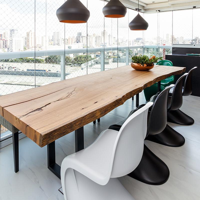 Mesa de jantar em madeira maciça com pés em aço carbono, acompanhada de cadeiras multi coloridas