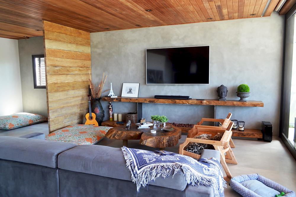 Combinação de mesa de centro de madeira maciça em bolacha e aparador com borda orgânica dão aconchego ao ambiente.