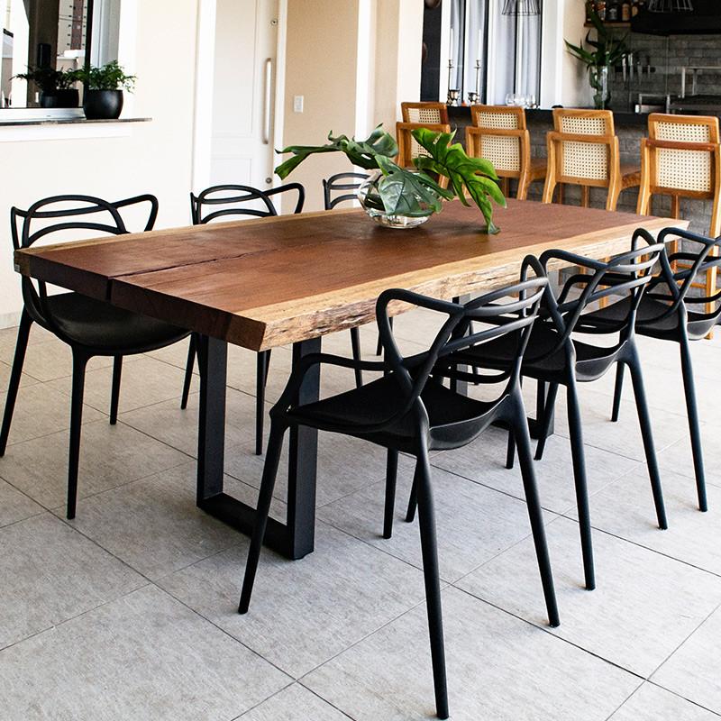 Mesa de jantar em madeira maciça de Jatobá com pés em aço carbono, acompanhada de cadeiras de pretas