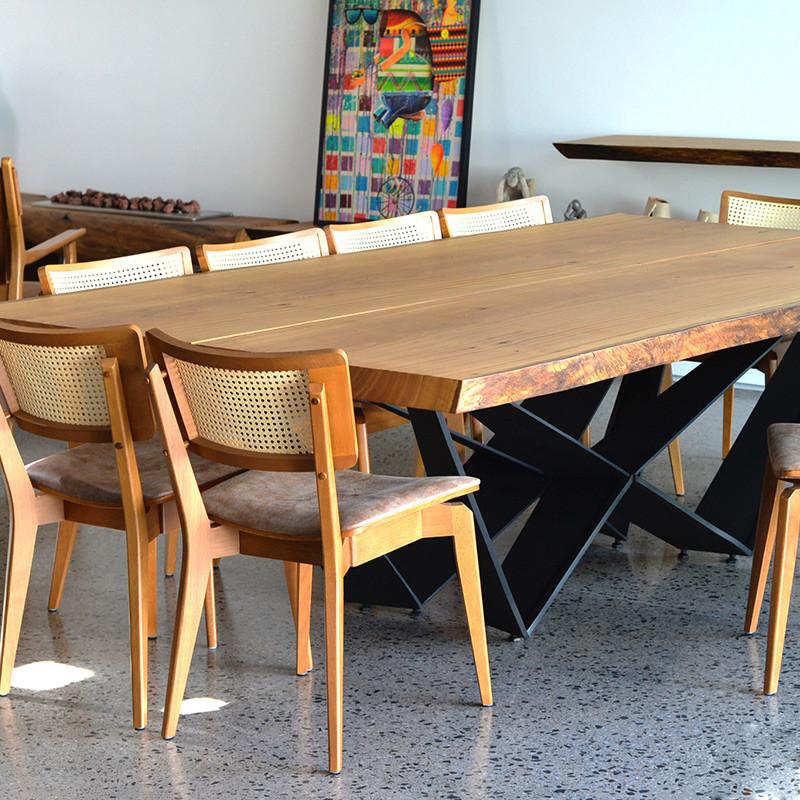 Mesa de jantar em madeira maciça com pés em aço carbono, acompanhada de cadeiras de madeira