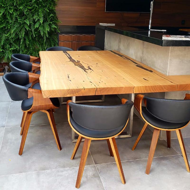 Mesa de jantar em madeira maciça, acompanhada de cadeiras que combinam madeira e estofado preto