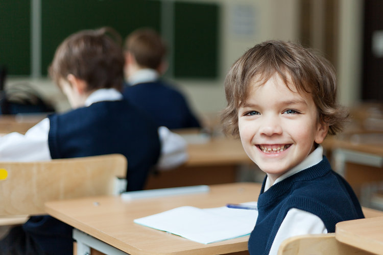 Happy Pupil in uniform sitting at  desk