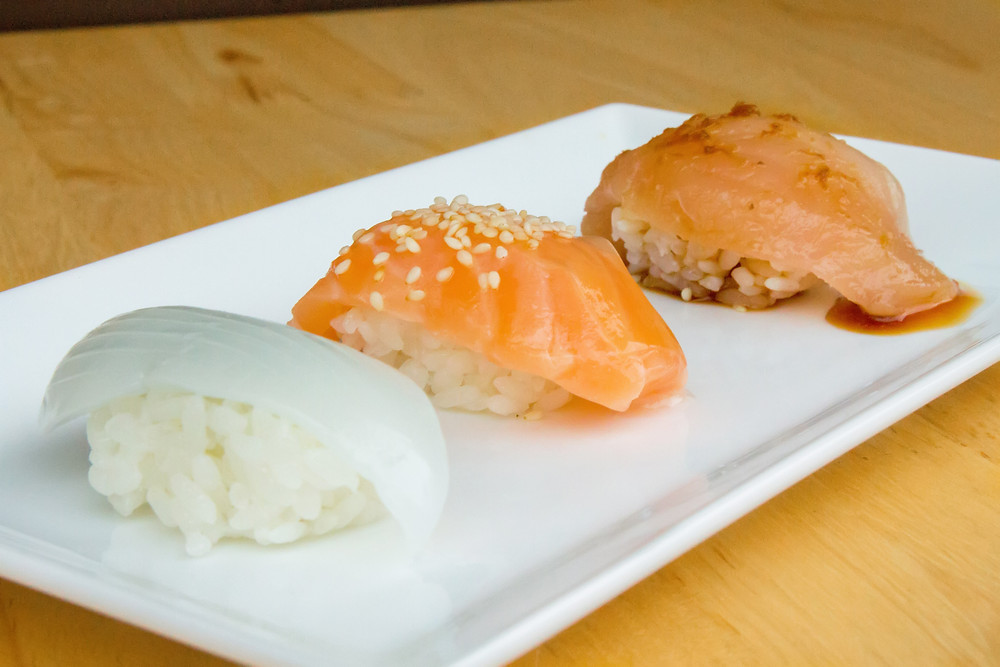 Three selections of Nigiri Sushi (varies daily. Squid, Salmon with lemon battera konbu white seaweed, and White Tuna Albacore with garlic ponzu sauce pictured). Mực ống, Cá hồi, Cá ngừ trắng