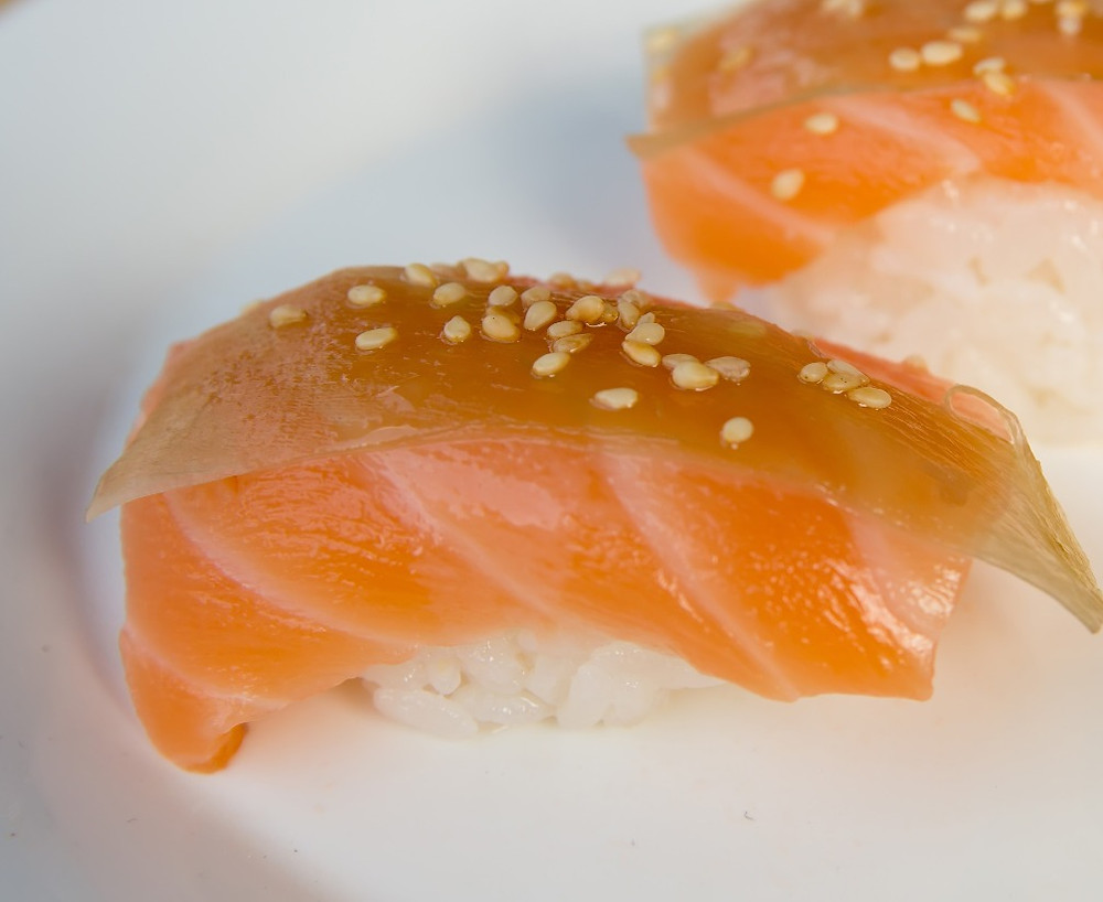 Salmon Nigiri Sushi with lemon, battera konbu (white seaweed), and sesame seed. Cá hồi