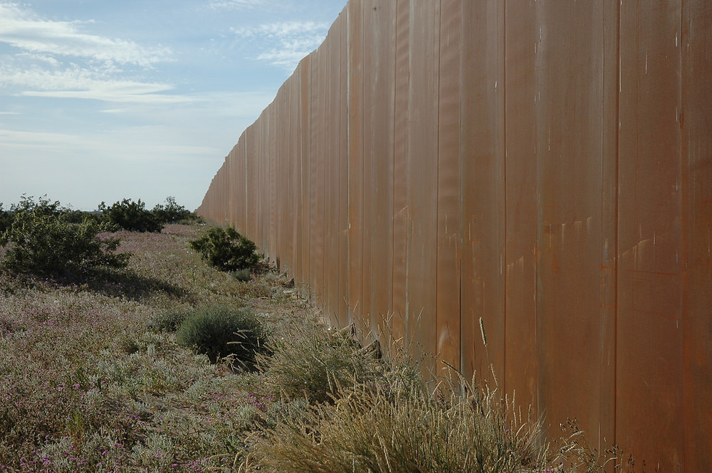 The wall along the Mexican border beside Highway 2. Photo credit: flickr.com