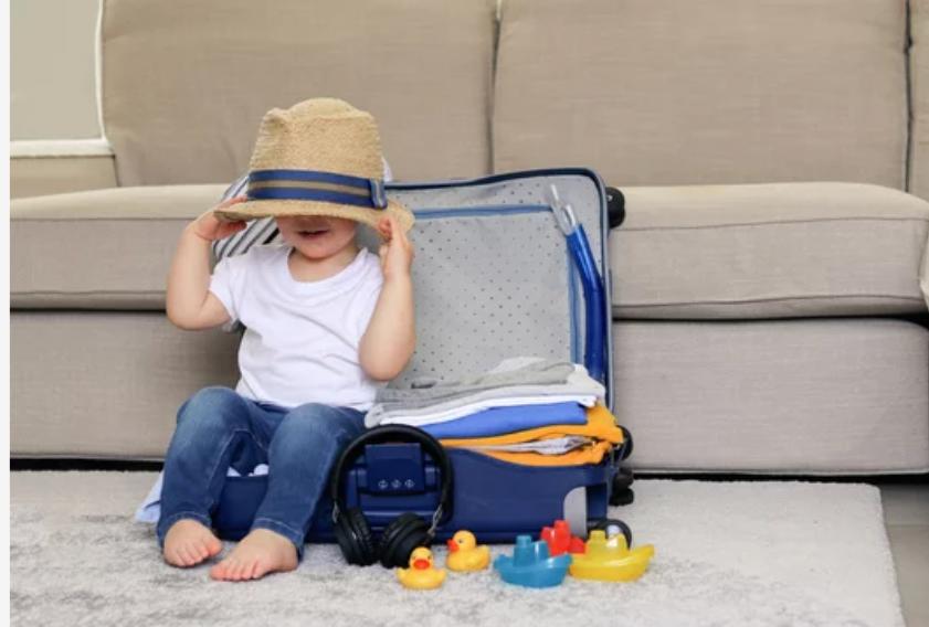 Bébé prêt à partir en vacances avec une valise