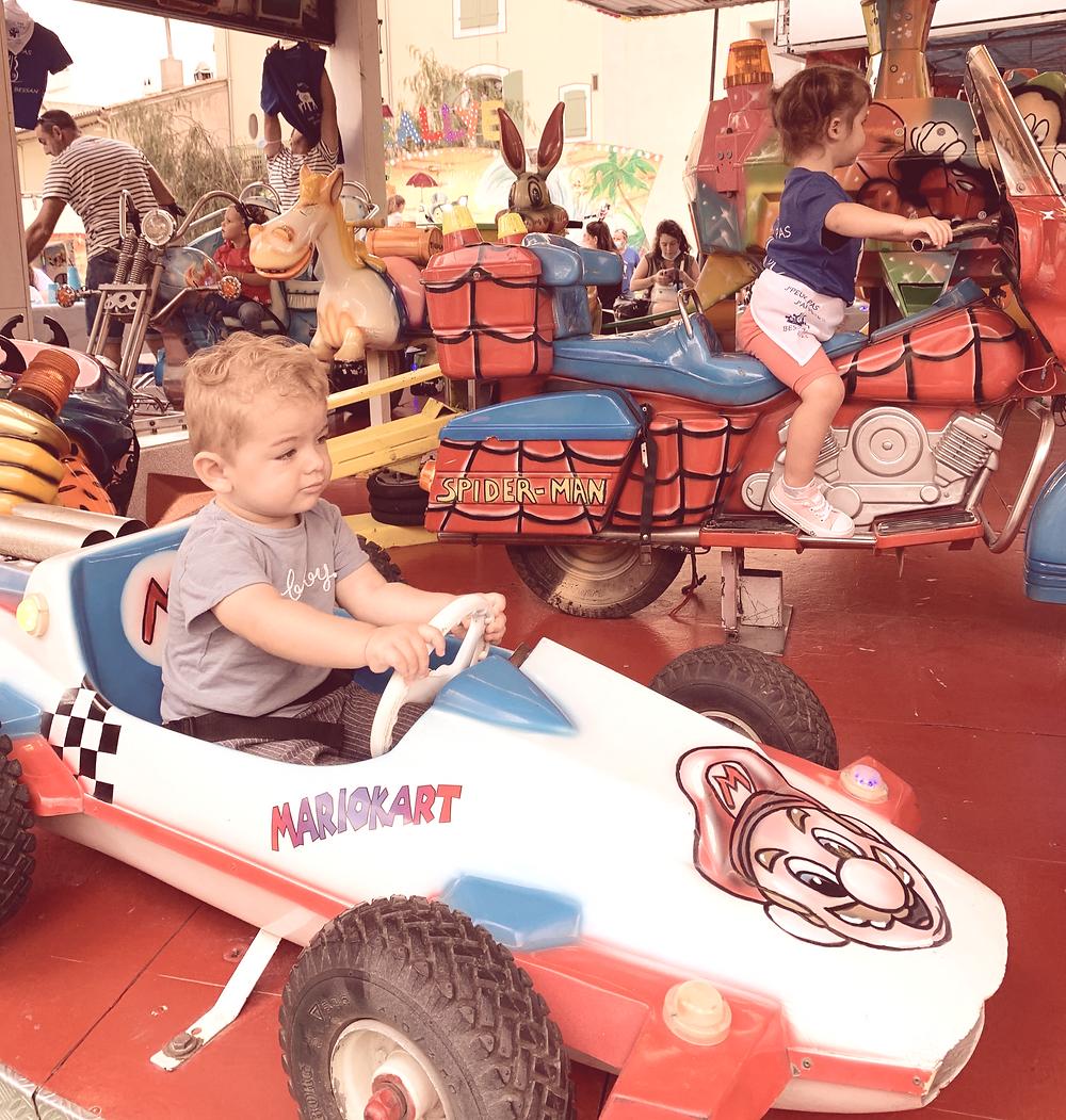 Bébé qui conduit une voiture à la fête foraine