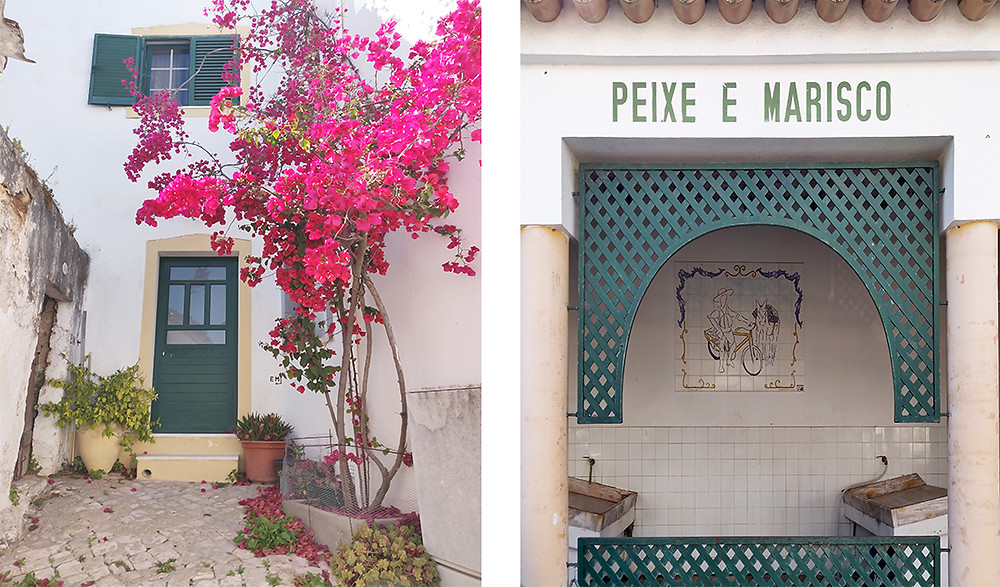 Whitewashed building with pink flowers and a fish market stand in Alte, Algarve.