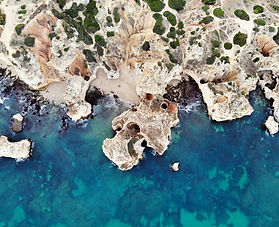 drone photography of a beach with cliffs and blue water in algarve
