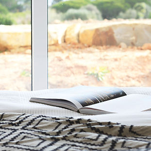 an open book laying on a bed with nature view in the background