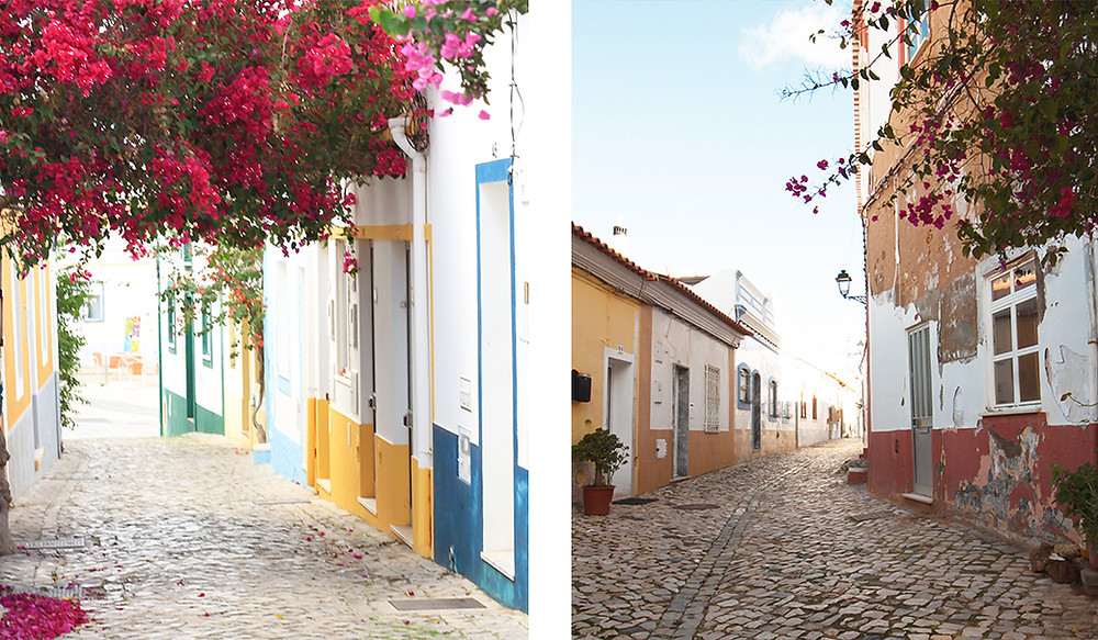 Pink flowers and colourful houses lined up in a cute street in Ferragudo, Algarve