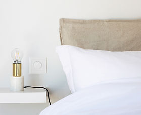 a bed with white and beige pillow