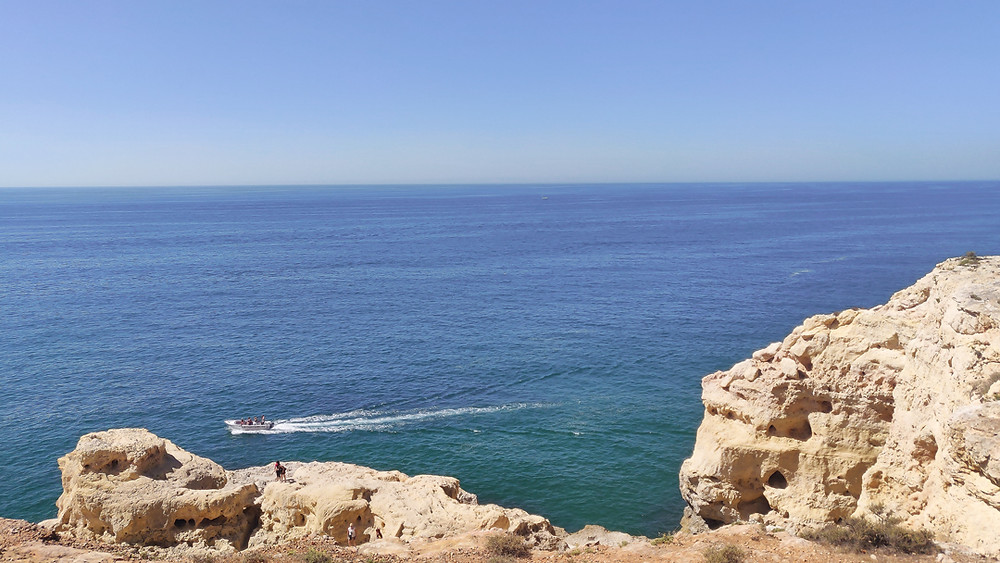 Big white and yellow cliffs, rock formation and caves set against the blue Atlantic ocean at Algar seco