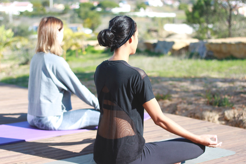 two girls on a terrace doing yoga and looking at the countryside view