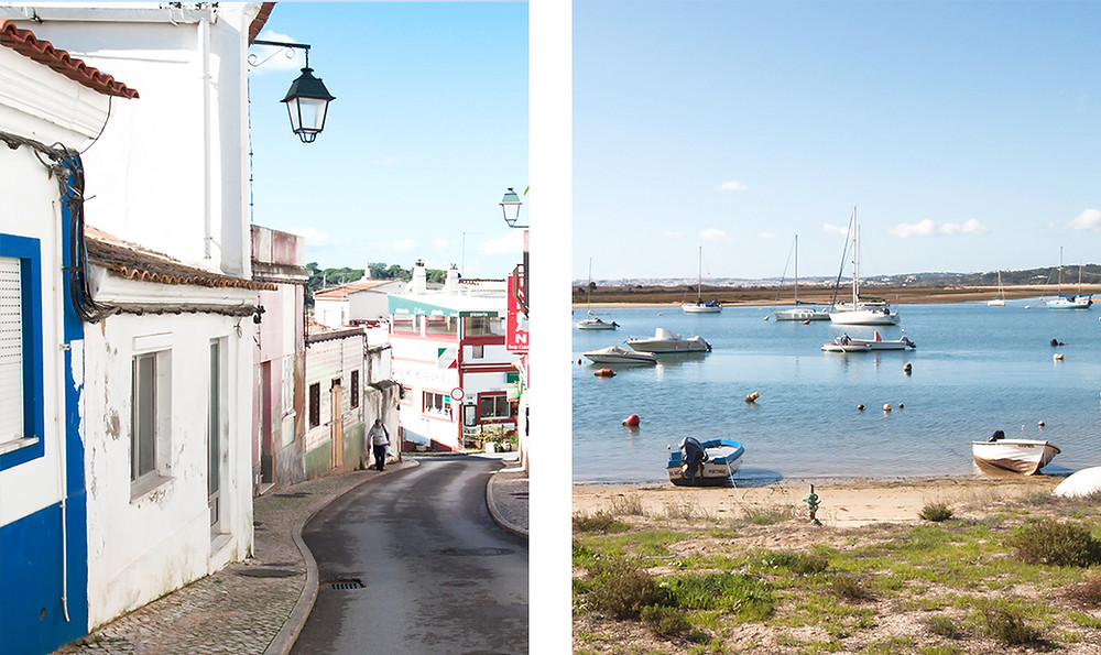 Narrow street with cafés and restaurant and fishing harbour with boats in Alvor, Algarve