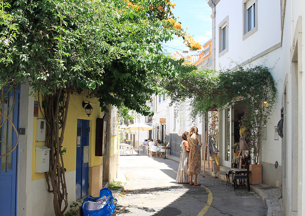cute street with shops with colored houses and flowers in Tavira