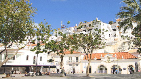 Trees, peple and whitewashed buildings at the main square in Albufeira, Algarve