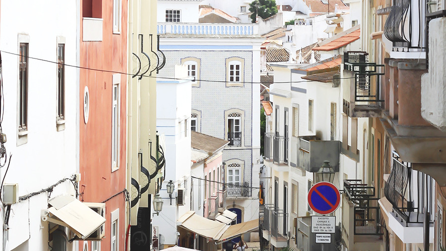 Street in Lagos, Algarve filled with beautiful buildings, restaurangs, shops and cafés