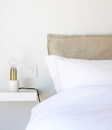 Bed with white bedding, golden light and beige pillow