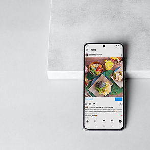 a mobile phone on a grey marble background showing a instagram feed