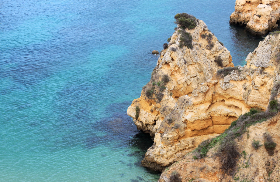 Blue water beach with yellow cliffs in Algarve