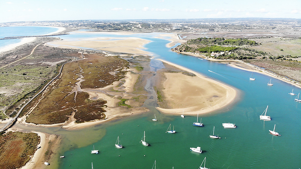Sand banks, boardwalk for birdwatching, river and small fishermen's boat in Alvor, Algarve