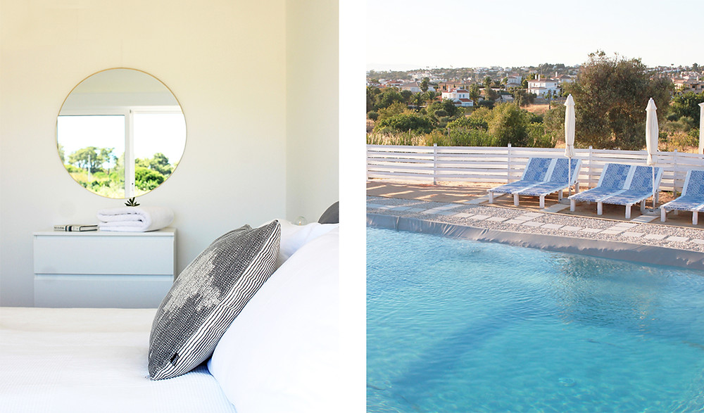 A room with a bed and mirror and a pool with clear blue water