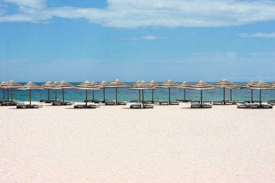 A beach with white sand, sun beds and huts. Blue water in the background with blue sky