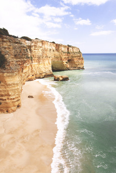 A beach in Algarve with limestone cliffs, green water and sand