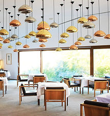 a restaurant with wooden chairs, lights with golden pendants