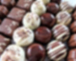 Selection of milk and white handmade chocolates in alternating lines of truffles and chocolates