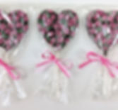 A display of heart shaped chocolate lollipops decorated with a rose pattern