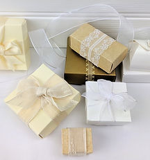 Cream and natural coloured ballotin boxes for chocolates with ribbons